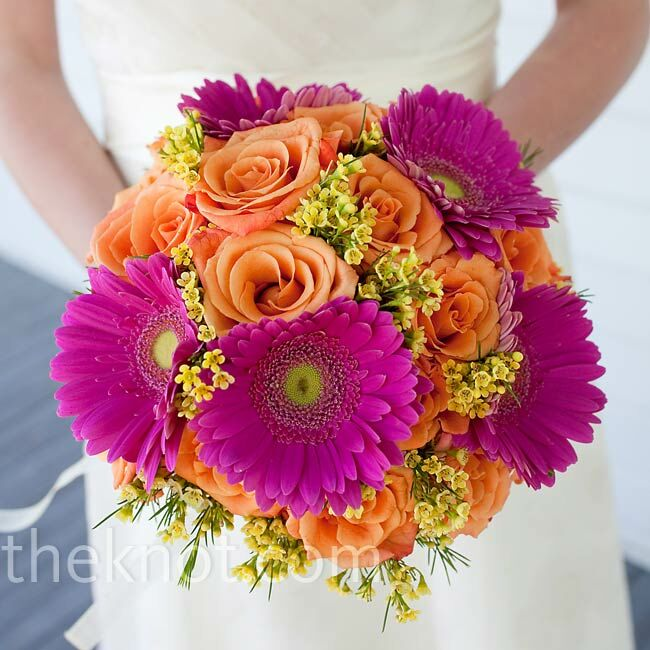 Deborah's bouquet was a bright mix of orange roses, pink daisies, and yellow wax flowers. The stems were tied with ribbon and rings from her two grandmothers.