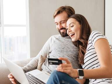 couple looking on computer and holding credit card