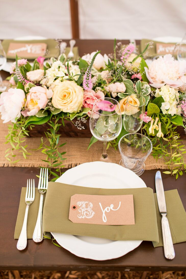 The reception tables combined both romantic and rustic touches. Each table was lined with a burlap table runner, covered with lush arrangements of peach and pink blooms including roses, peonies, astilbe and calla lilies. Pinky-peach place cards added a pop of color to the earthy brown linens.