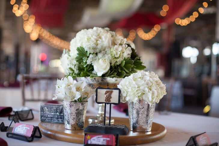 White hydrangeas and alstroemeria flowers were arranged in vintage mercury glass vases to create each centerpiece.