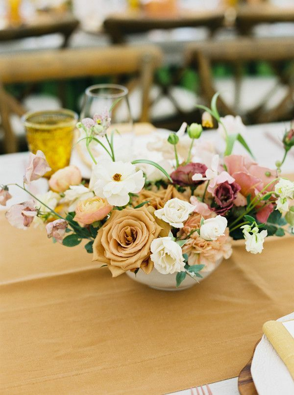 Floral centerpiece on top of mustard-yellow table runner