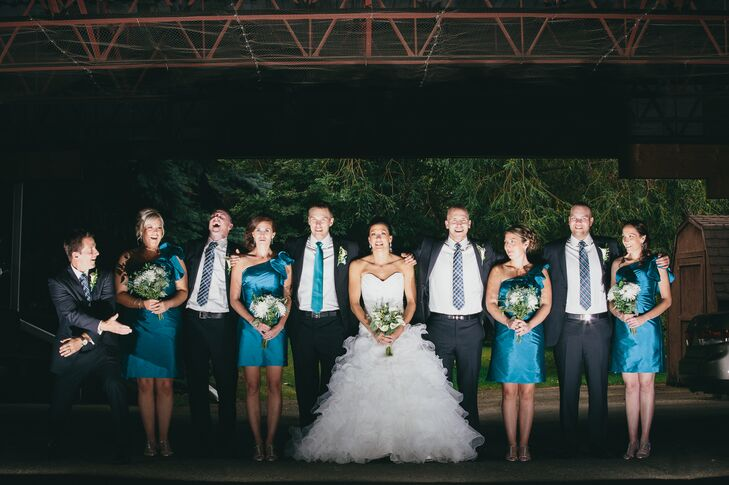 The bridesmaids wore teal one-shoulder dresses which matched the teal ties that the groomsmen wore with the black suits.