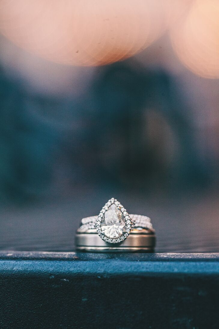 Christina's stunning pear-shaped diamond engagement ring with a diamond halo and band and Neil's silver wedding band look beautiful together.
