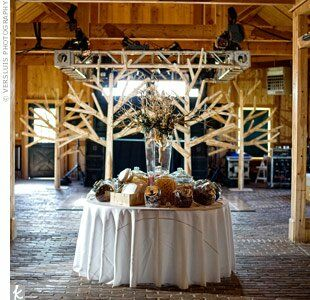 On the candy table, a contemporary glass vase filled with Manzanita branches complemented the natural elements of the barn.