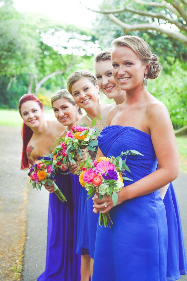 The bridesmaids all wore short, royal blue dresses that were either strapless or one-shoulder, and they complemented them with a pair of strappy silver heels. The maid of honor wore a full-length version of the same dress with a jeweled belt to stand out, and they all carried smaller versions of the bride's colorful bouquet.