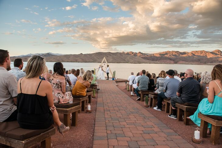 Christa and Jesse exchanged vows at dusk at the newly renovated Havasu Springs Resort in Parker, Arizona, on a cliff that overlooked Lake Havasu. To add even more ambiance, the aisle was lined with oversize candles filled with desert sand.