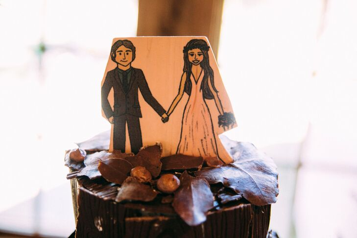 The bride hand drew portraits of herself and Andrew for the invites and printed the illustration on a piece of wood for their cake topper.