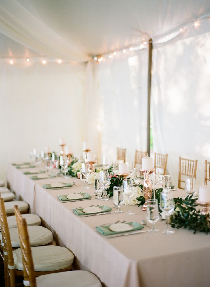 """""""Our reception was exactly how we envisioned it,"""" Jamie says. """"We dressed up our tent with draped fabric and crystal chandeliers, and our centerpieces included a lot of candles to achieve a romantic and intimate ambiance."""" Tables were cloaked in soft pink linens and surrounded with elegant gold chiavari chairs."""