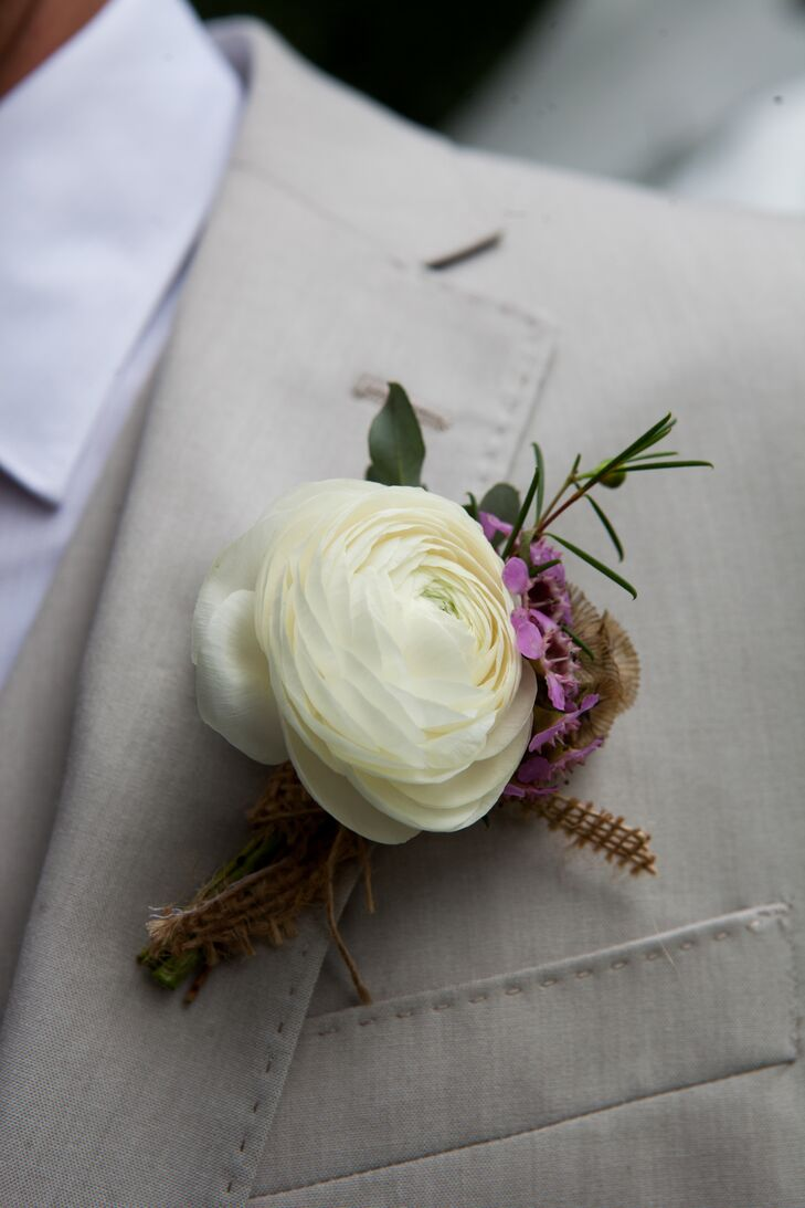 The groom's boutonniere was created by New Creations Florals using a white ranunculus, purple wax flowers and scabiosa pods with burlap wrapped around the base.