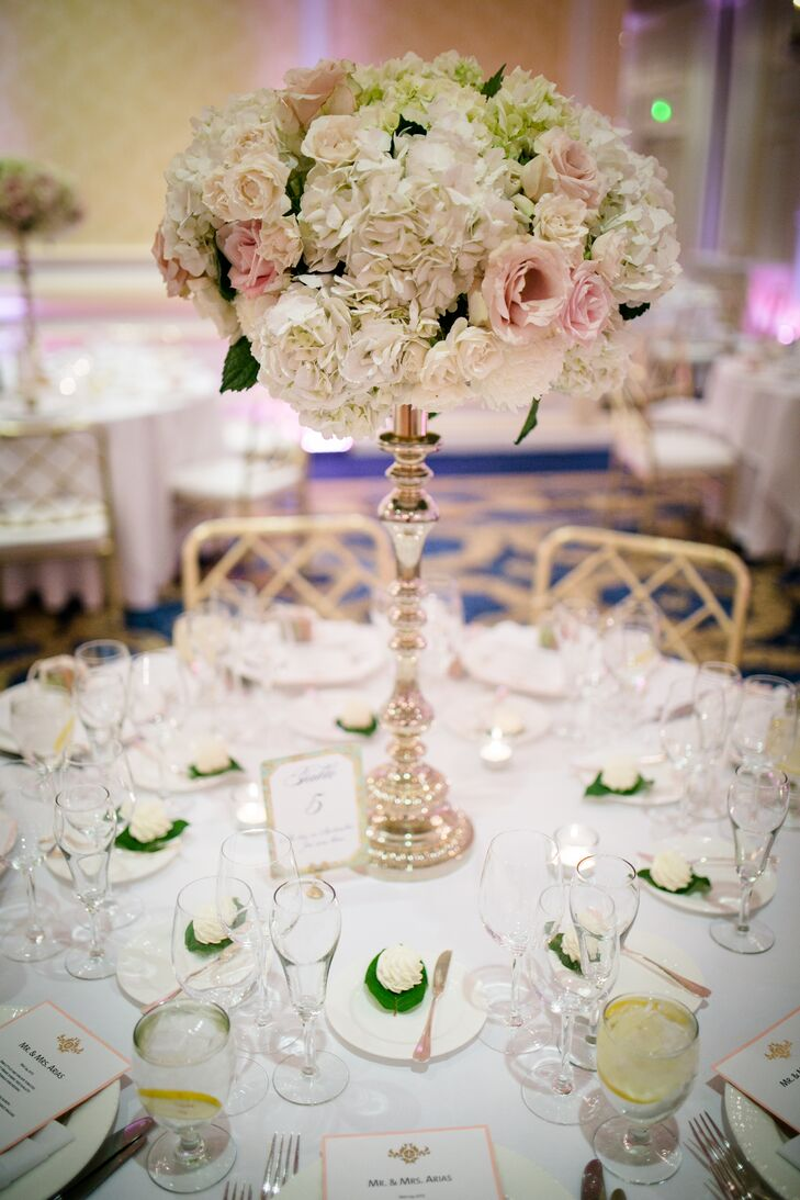 To bring Rebecca and Jonathan's opulent, spring theme to life, Mimosa Floral Design created arrangements of lush seasonal blooms displayed on elegant silver candelabra pedestals. Ivory hydrangeas, chrysanthemums and blush roses and spray roses infused the room with a soft, romantic feel, while tying into the evening's classic, timeless vibe.