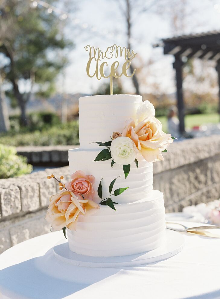 Flour House Bakery created Brittany and Bailey's simple three-tier cake, which was decorated with peach and ivory blossoms as well as a gold topper.