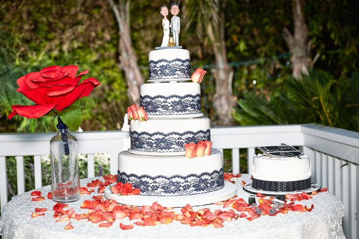 The lemon raspberry chiffon wedding cake stood four tiers tall, each wrapped with navy lace at the bottom. The cake was accented with coral roses and topped with figurines portraying Shirley, Patrick and their dog.