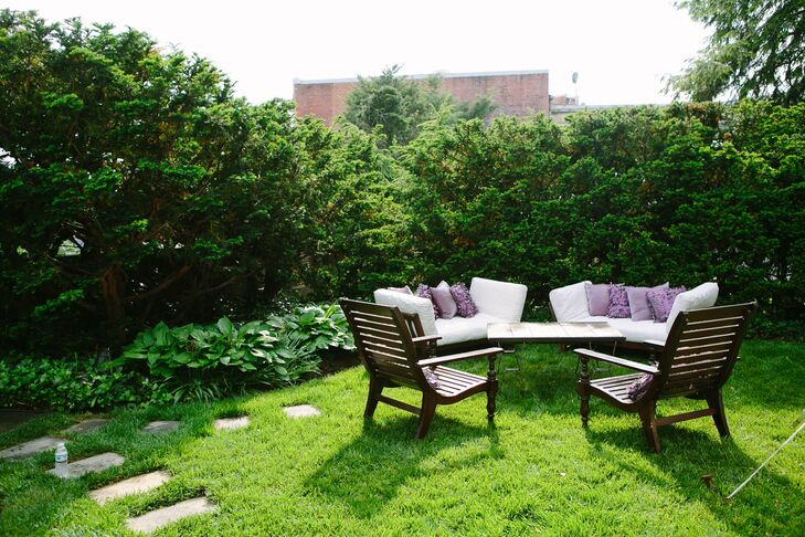 Wooden furniture with white and lavender cushions sat just outside the tent so guests could enjoy the lush gardens.
