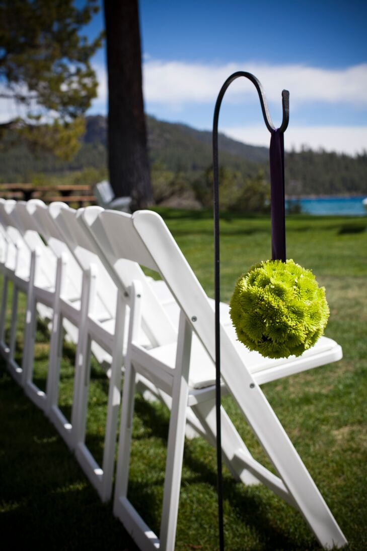 Green chrysanthemum pomanders hung from hooks lining the aisle for a pop of bright green against the natural backdrop of the Lake Tahoe waterfront wedding ceremony.