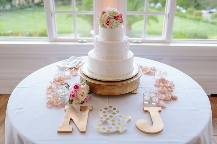 The three-tier wedding cake featured flavors of lemon, raspberry and chocolate. A gold cake stand and decorative letters went with playful, feminine style.