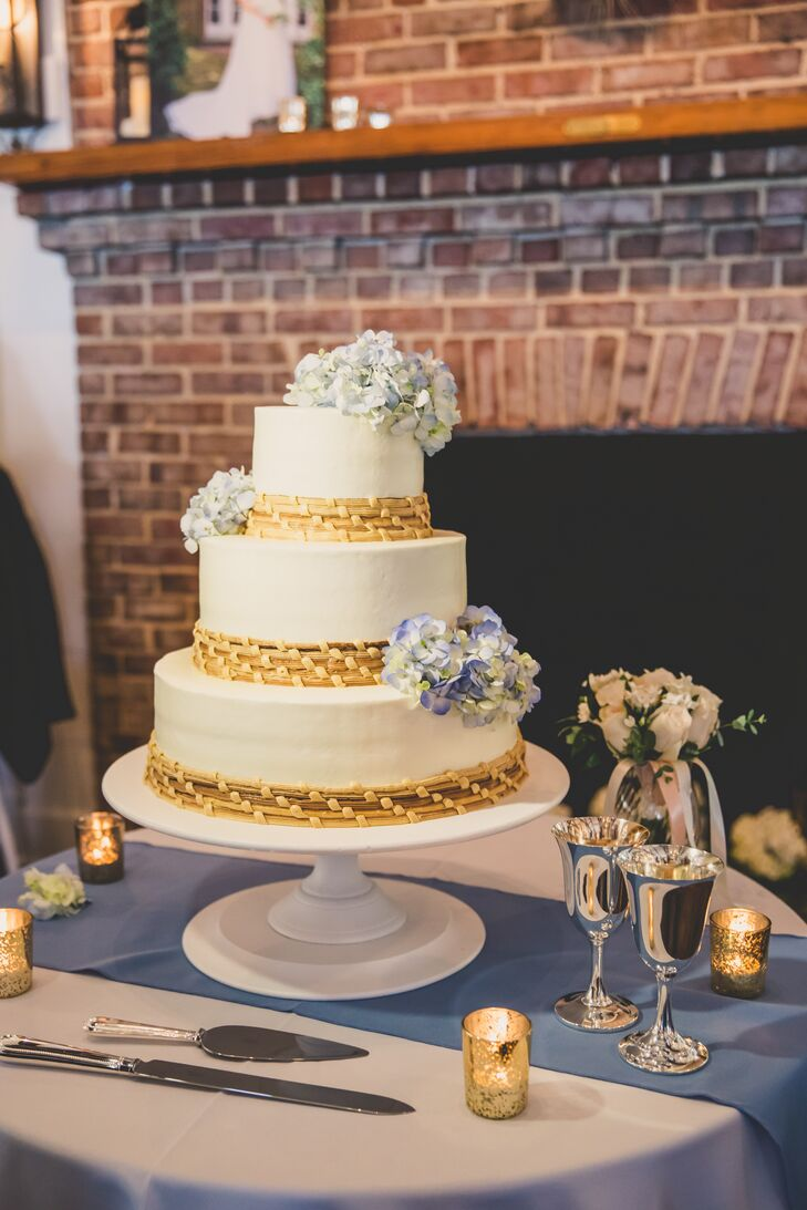 The white wedding cake for dessert was decorated with blue hydrangeas and accents of sweetgrass basket weaving, a craft native to the lowcountry regions. The cake was displayed on an antique white cake stand on a blue and white cake table.