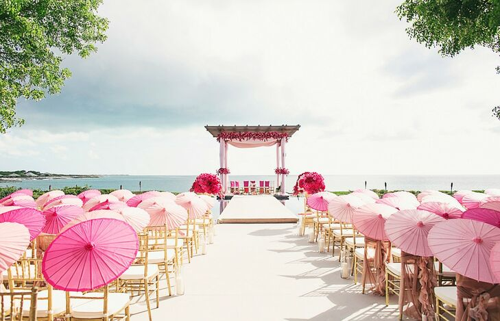 "To keep the focus on the striking beauty of the  Amanyara resort in Turks and Caicos, Melanie and Neeraj kept the ceremony decor more simplistic. Using gold chiavari chairs and parasols in shades of pink, planner Sonal Shah created an ombre effect leading to the mandap. The mandap was draped in blush pink fabrics and highlighted with bright pink flowers. ""It was important for us to keep the decor elegant and not compete with the natural beauty of the surroundings,"" Melanie says. ""I got emotional when I witnessed the whole thing come together in person. It was a dream!"""
