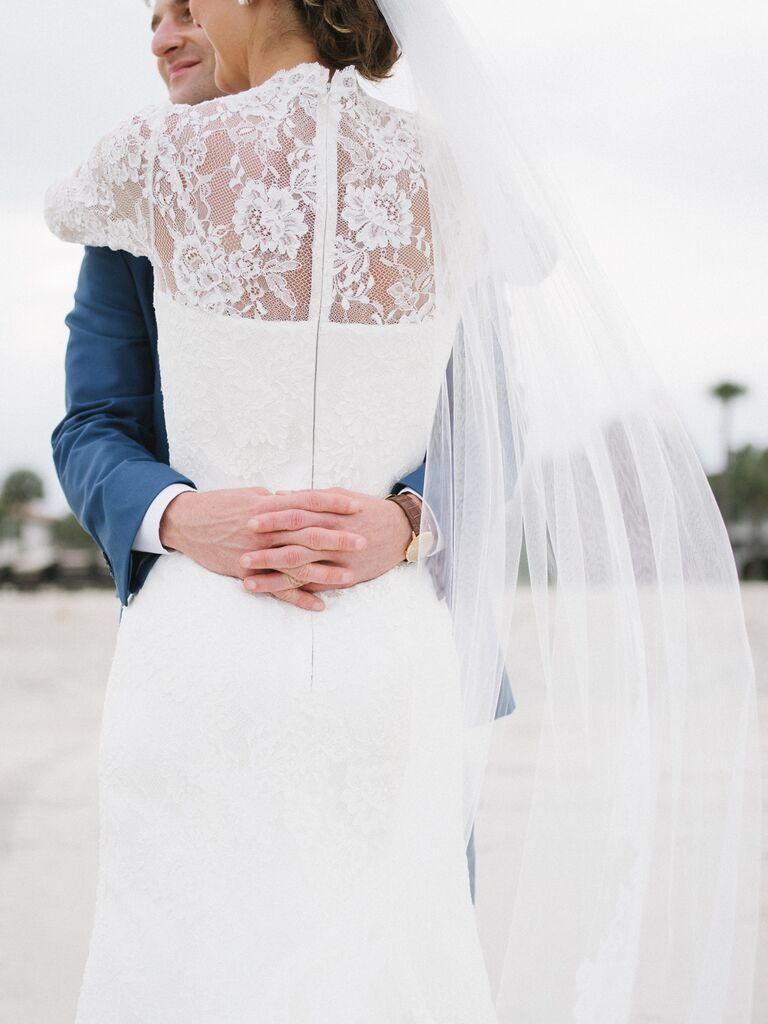 Long-sleeved lace wedding dress with chapel-length veil