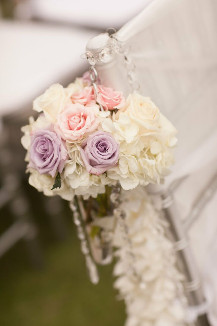 Purple and pink roses mixed with white hydrangeas and clear beads for an elegant aisle marker at the ceremony.
