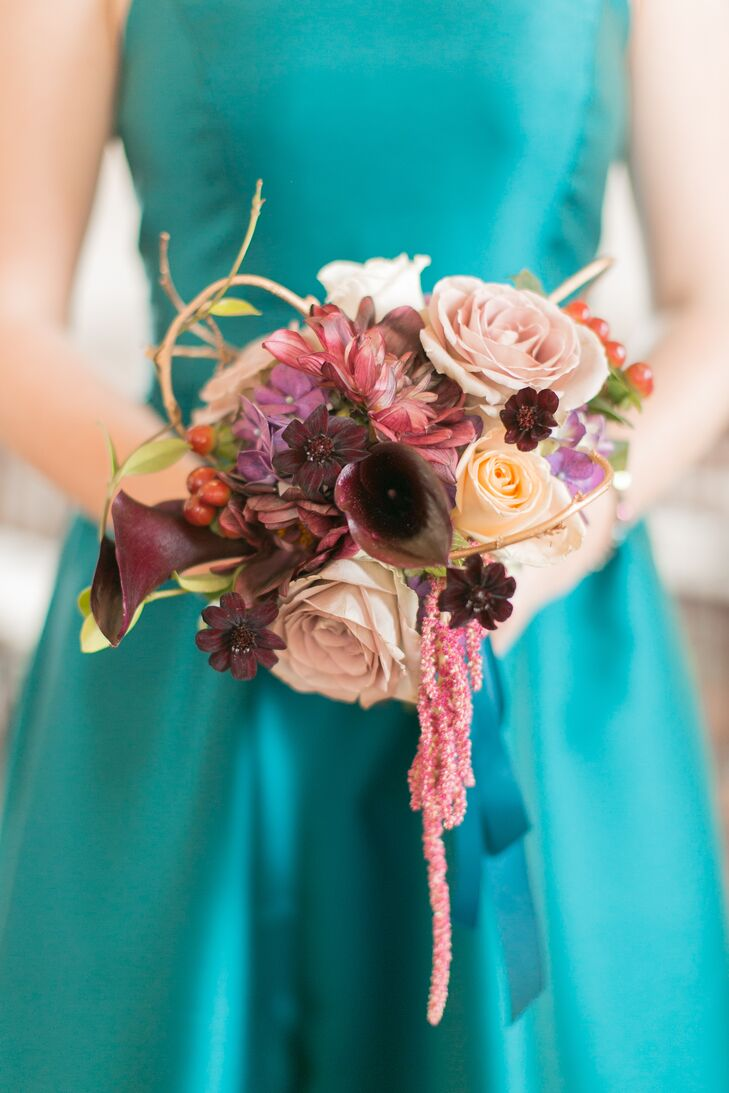 Similar to Beth's bouquet, the maid of honor's bouquet had fall-hued florals set against the backdrop of her jewel-tone full-length teal gown.