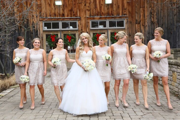 Lisa wore an ivory ball gown wedding dress with a sweetheart neckline and tulle skirt. Her bridesmaids wore knee-length lace dresses in a champagne color, following the color palette. They each held a smaller version of the bride's ivory and pink bouquet, which was made of roses, calla lilies and silver brunia.