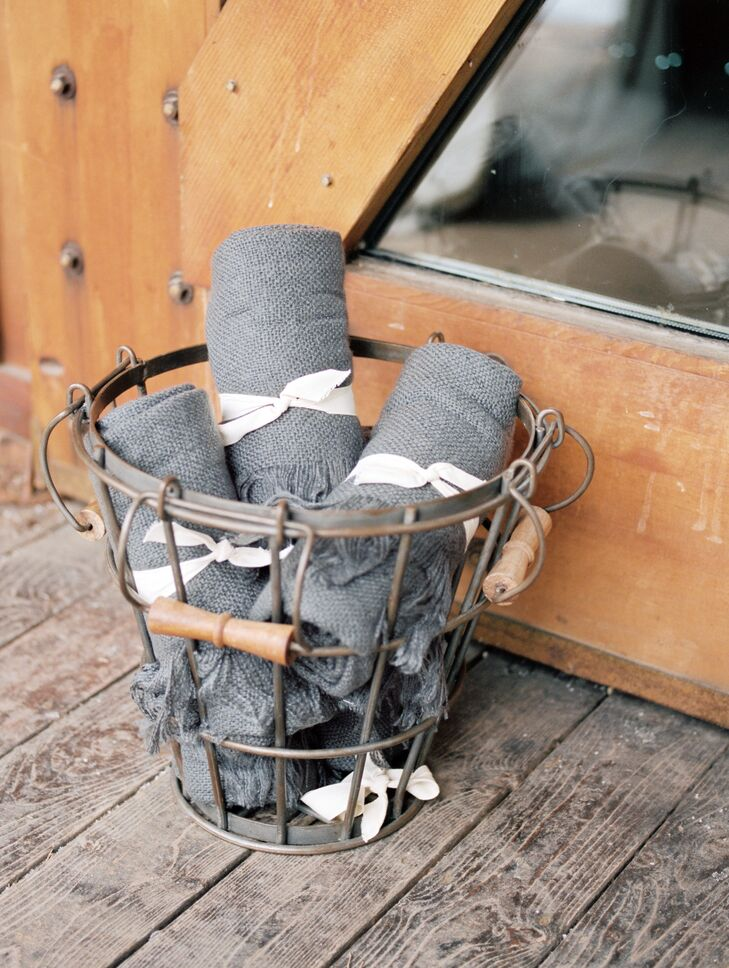 Guests kept warm with wire baskets filled with gray throw blankets.