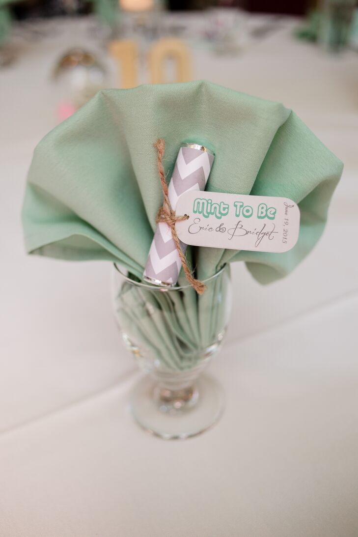 """Mint wedding favors wrapped with gray and white zigzag designs followed the color scheme of the wedding perfectly, with a mint green napkin backdrop! The tags attached to the favors read """"Mint to Be"""" along with Bridget's and Eric's names."""