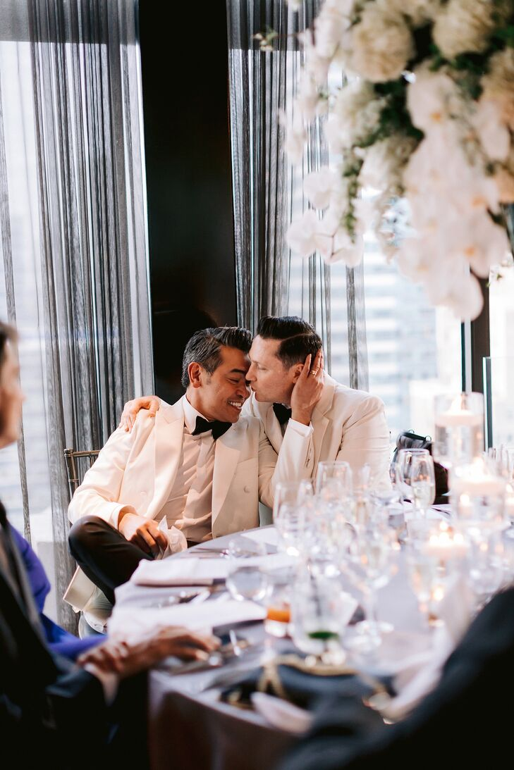 Elegant Grooms in White Tuxedos at Restaurant Reception