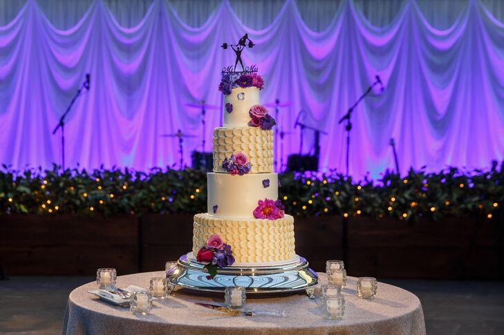The four-tier cake was displayed on a silver stand, covered in buttercream frosting and decorated with fresh flowers to match the reception's arrangements. The sweet dessert had textured designs on alternating layers, created by Kelsey Elizabeth Cakes.