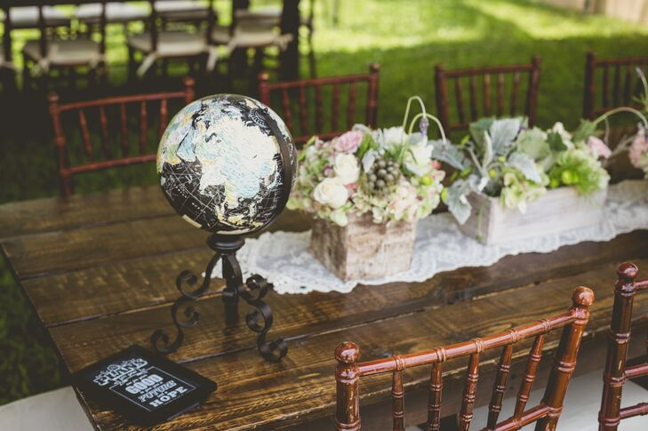 Roxy and Rodney's vintage style definitely came out in the reception decor. Guests took their seats among family-style wood tables topped with flowers, lace runners and a few unexpected details, including a chic black globe.