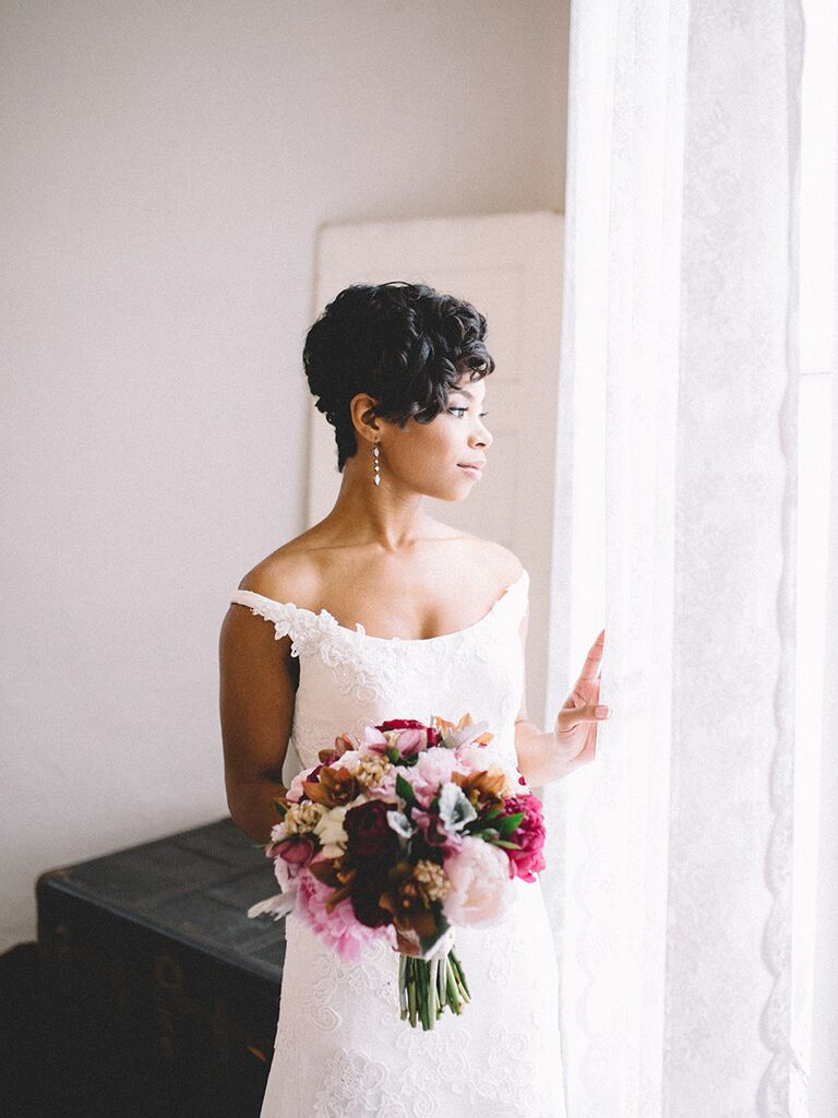bride wearing off-the-shoulder dress holding a romantic bouquet