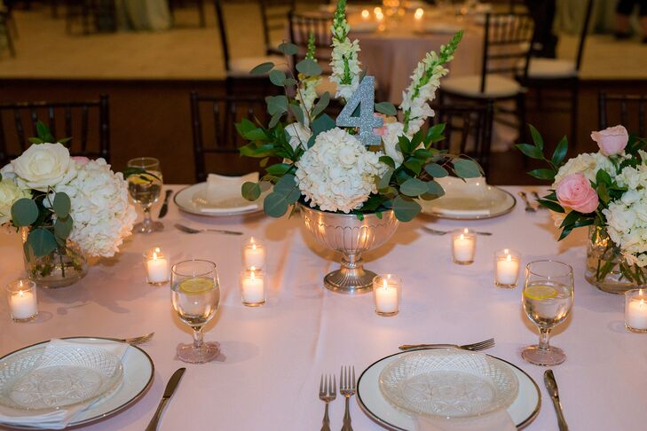 Silver urns were filled with white hydrangeas and green eucalyptus leaves for a lush look that matched the garden theme. Elizabeth and Tim put the sparkly silver tables numbers into the arrangements. The surrounding candles added plenty of romance to the space.