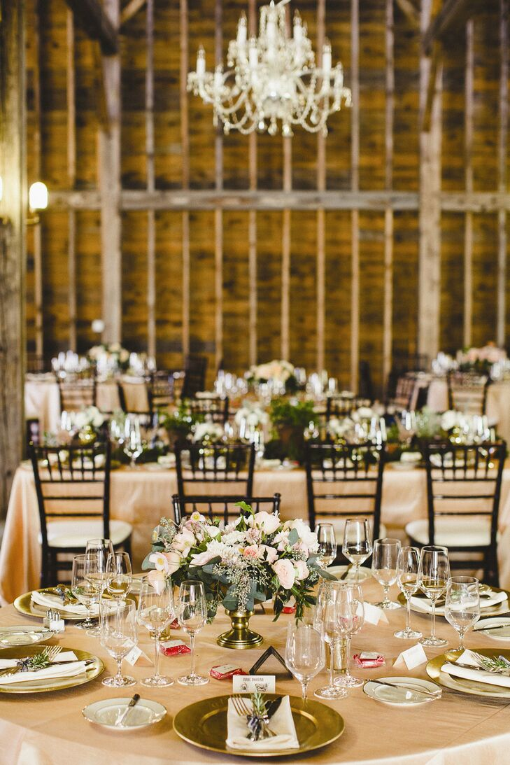 Peach and white roses, daisies and dahlias were displayed in brass urns for the round table centerpieces.
