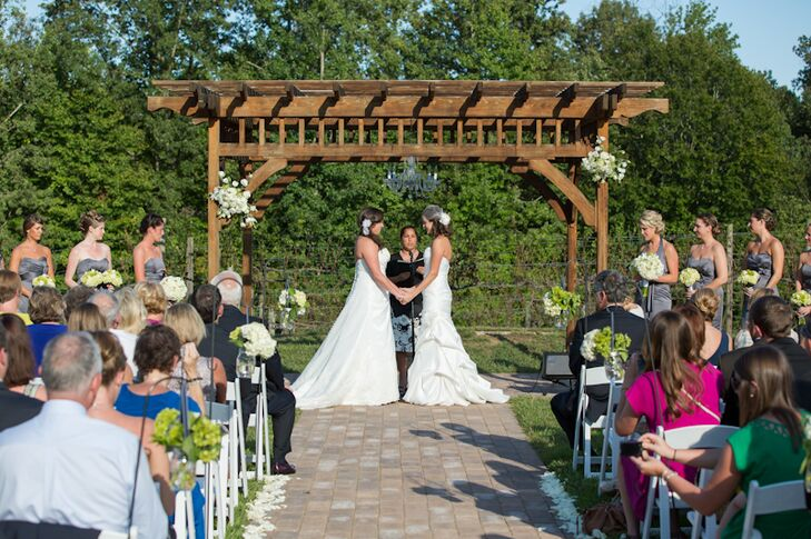 Jenna Nobles and Jenna Reich were married under a wooden pergola at Running Hare Vineyard. The pergola was decorated with white flower arrangements and the brick ceremony aisle was lined with white rose petals.