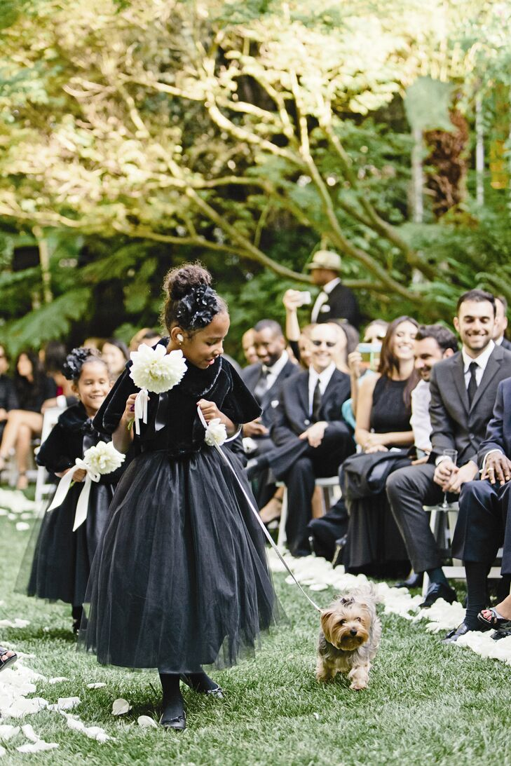 The flower girls wore black tulle dresses and glam fur shawls. Even the couple's dog was dressed for the occasion. Chloe's leash was decorated with white roses attached to her collar, Brittany says.