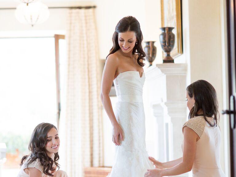 Bridesmaids helping bride in wedding gown