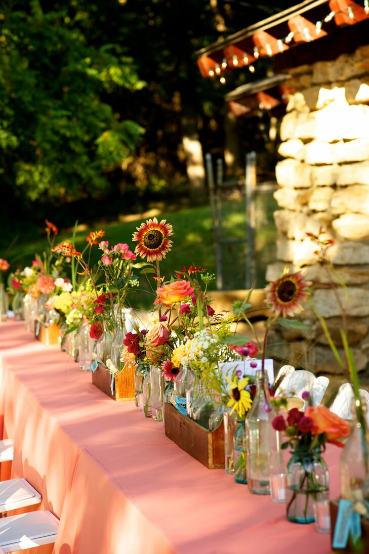 The centerpieces, made up of vintage bottles filled with colorful wildflowers, served as a living table runner when placed directly along the center of the eight-foot tables.