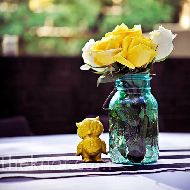 Vintage Mason jars were filled with yellow and white roses and accented with antique owl figurines.