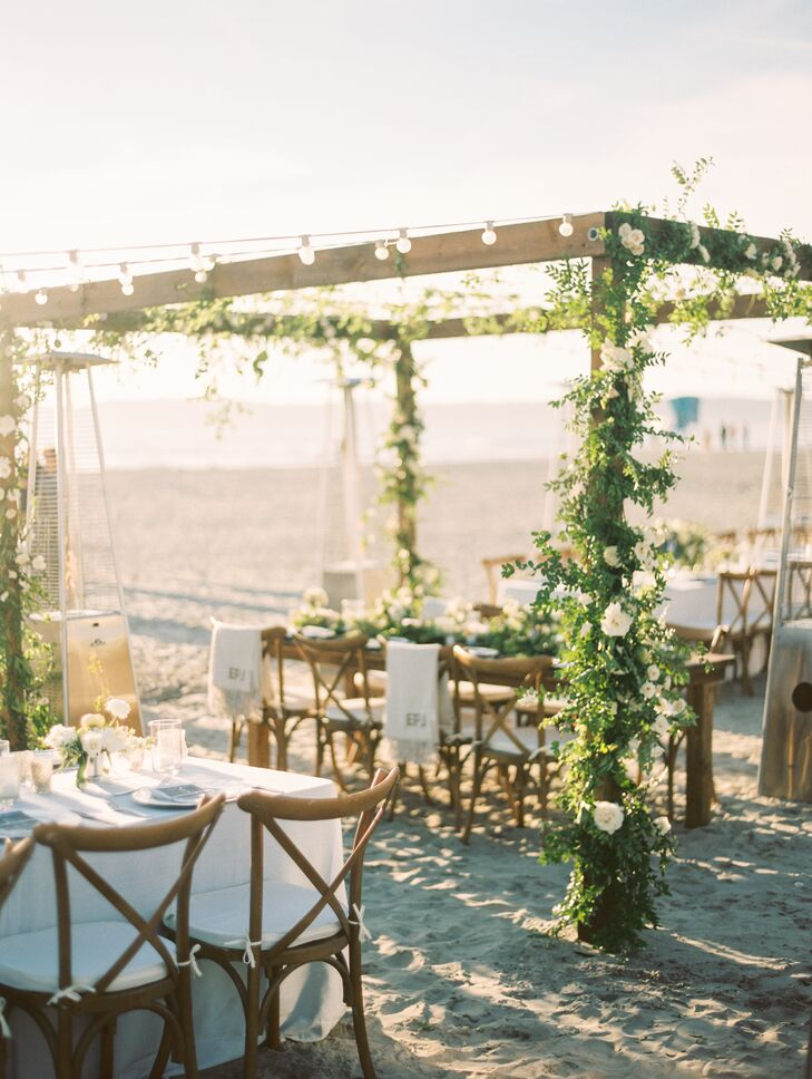 """We had these wooden arches covered in flowers and greenery and draped with market lights, which created a close, homey feel,"" Eliza says. Florist Blush Botanicals wound leafy greenery and gardenias up the posts of the arch, which was topped with string lights."