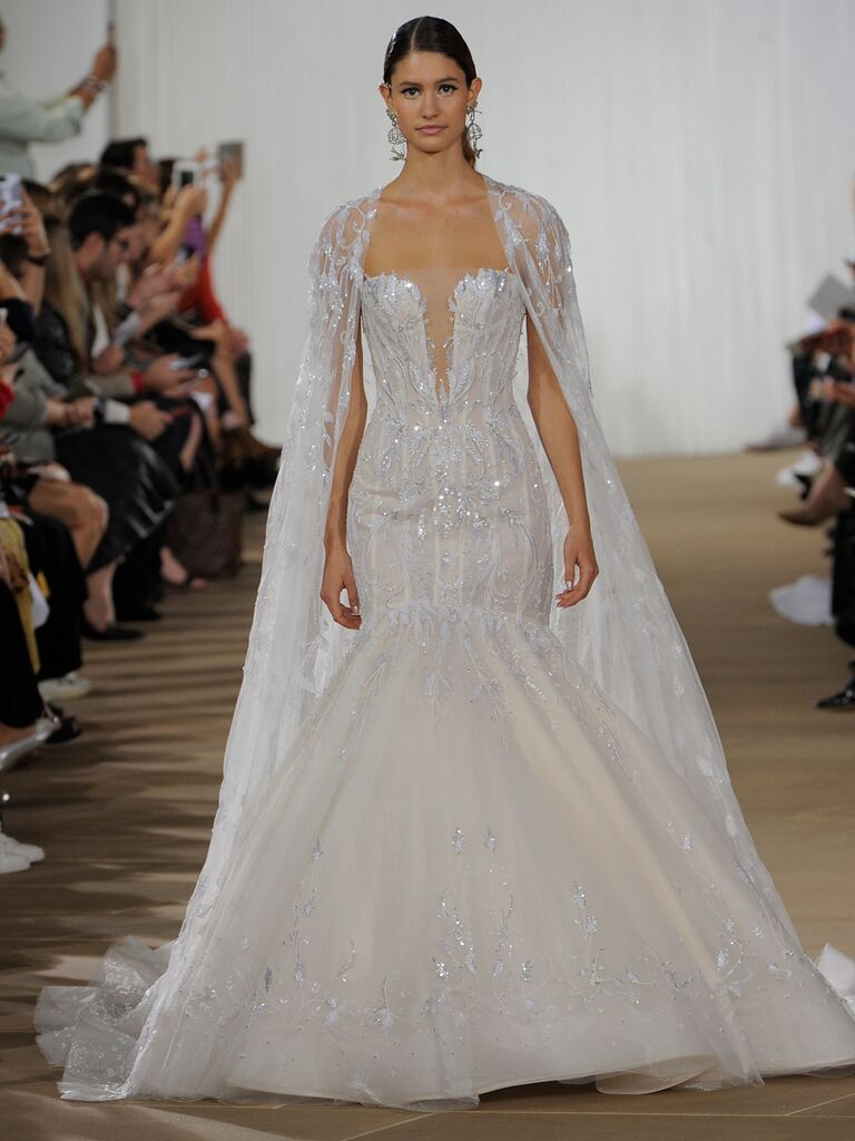 Ines Di Santo Fall 2019 wedding dress with a mermaid silhouette, plunging neckline and embroidered tulle cape