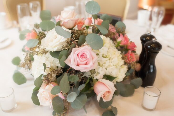Centerpieces at the restaurant reception were made up of low arrangements of pink roses, ivory hydrangeas, seeded eucalyptus and eucalyptus leaves.
