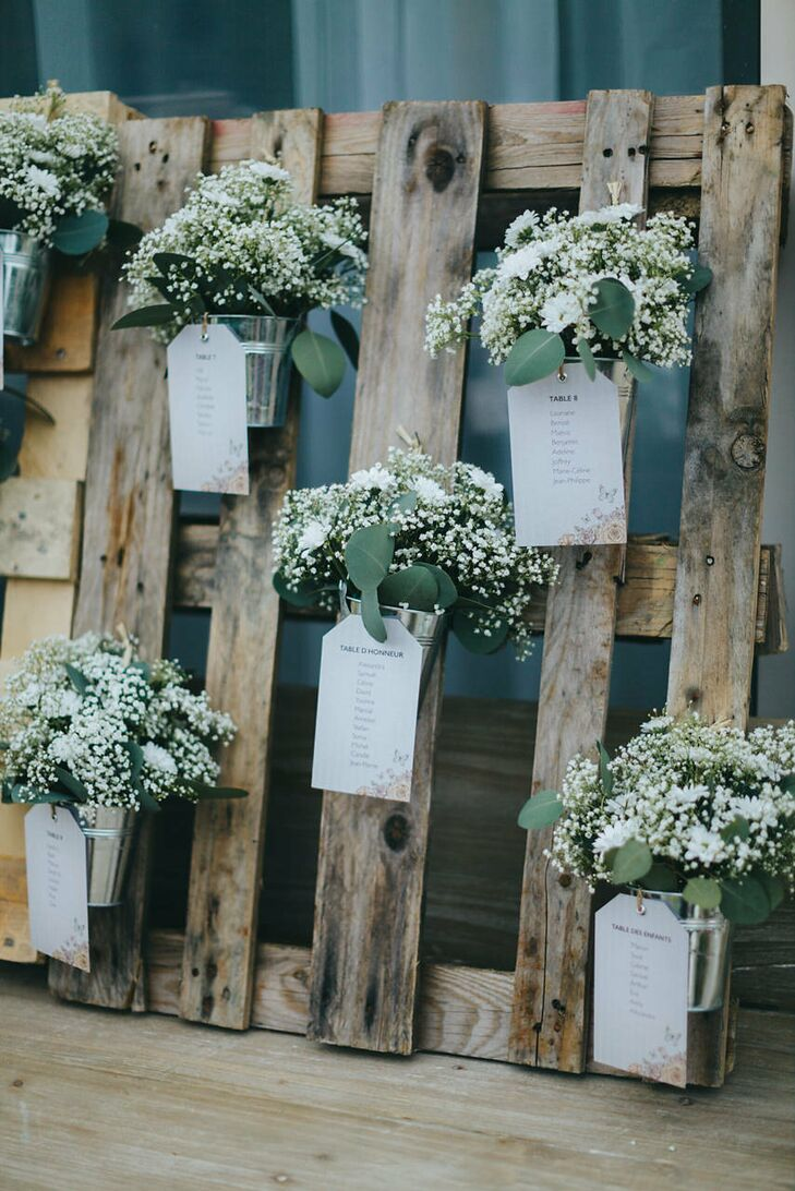 Table assignments were printed on floral printed card stock and fastened to tin buckets of delicate white flowers. Each pail was hanging off a wooden fence.