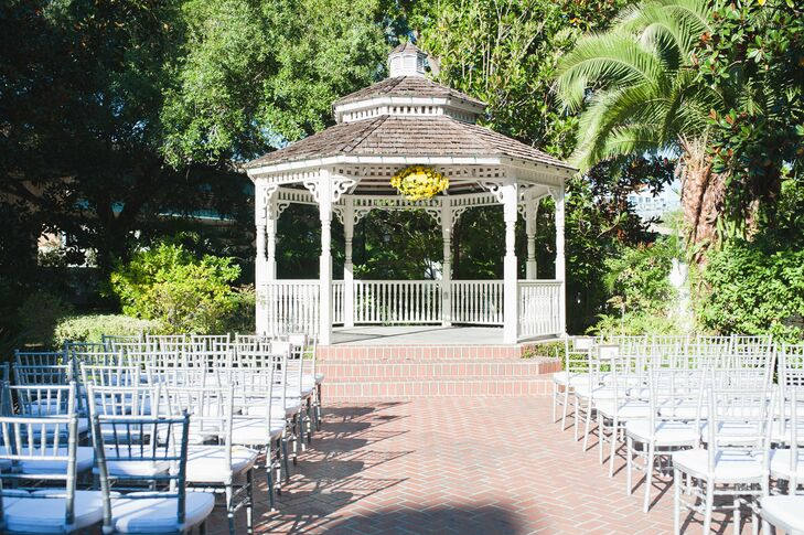 Kimberlee and Hegel got creative and brought all their wedding colors into the ceremony decor at the Courtyard at Lake Lucerne in Orlando, Florida. Their 70 guests watched the service from silver or white chiavari chairs. For a burst of color, they also had Jonathan's Flowers set up a hanging arrangement of yellow chrysanthemums along the gazebo.