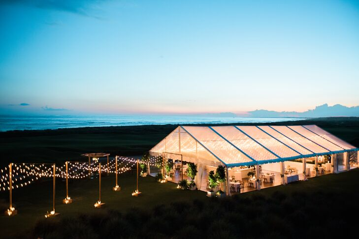 """A custom canopy constructed using posts, romantic string lights and bronze lanterns led guests from the ceremony to the tented reception for cocktail hour.  """"We also used lots and lots of string lights in the clear top tent as well as large trees to add interest and height and really make the tent feel like a room of its own,"""" says Caroline. """"The entire tent was floored with beautiful pine flooring."""" Caroline and Gil brought the outdoors in by adding potted trees and lush floral arrangements, while the clear-top tent gave guests a view of the starry-night sky."""