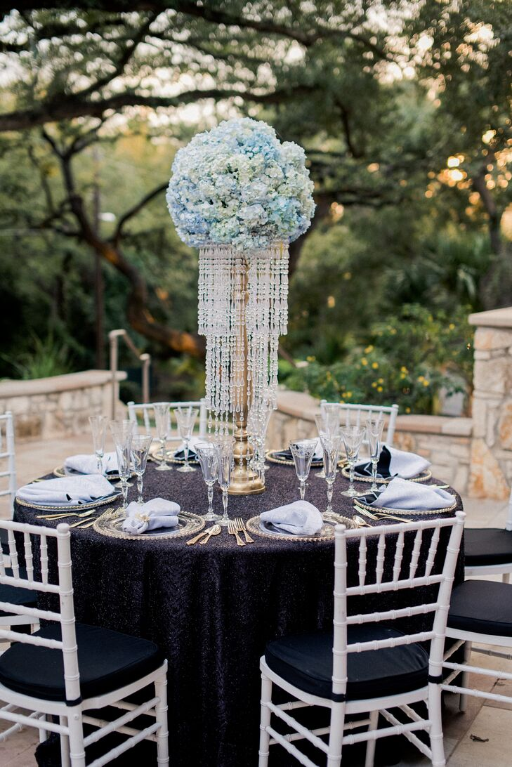 Ken and Pat created three centerpieces for the reception at Westwood Country Club in Austin, Texas, creating a textured, visually intriguing aesthetic. Bundles of brilliant blue hydrangeas were piled high atop gilded candelabras and surrounded by cascades of glittering crystal beads to achieve a refined look.