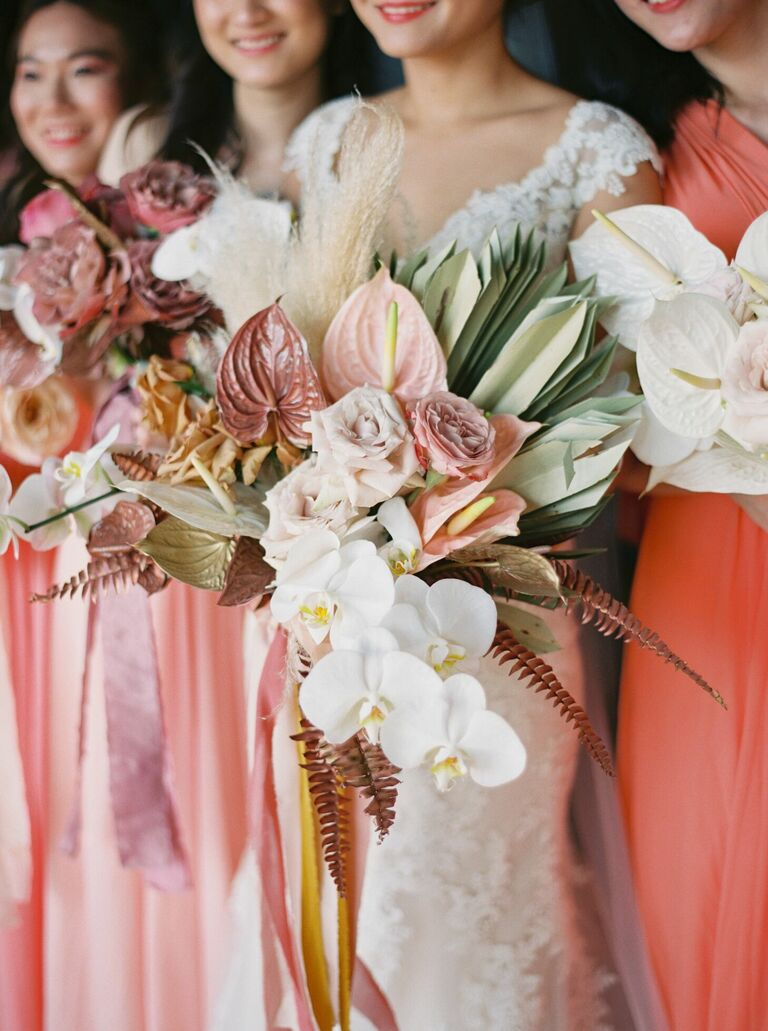 Bouquet with pink anthurium, white orchids and dried palm leaves