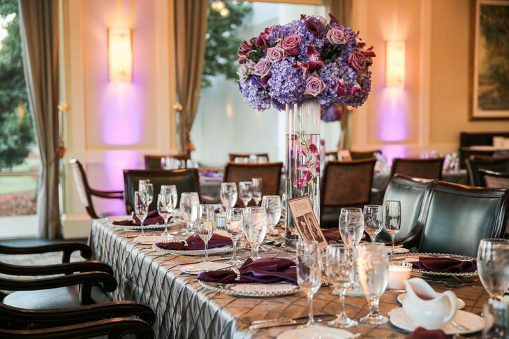 Basked in amber, pink or purple uplighting, each family-style table was met with a lush purple centerpiece designed by Beautiful Kreations, the couple's florist. Each tall floating orchid was matched with mauve and pink roses, pink orchids, purple calla lilies and blue hydrangeas stop a cylinder vase. Similar arrangements were also used as the couple's ceremony decor.