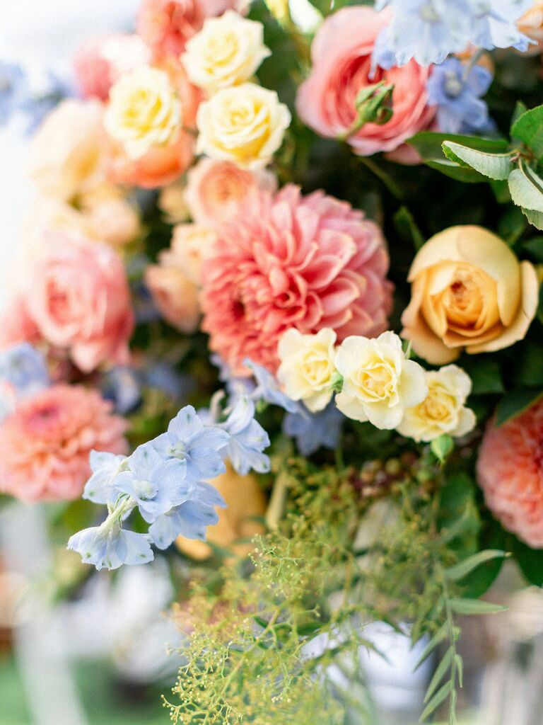 Pastel pink, yellow and blue flowers with sprigs of greenery