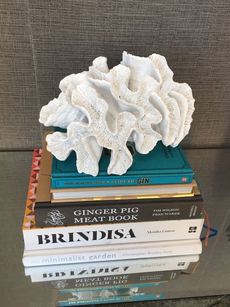 White resin faux coral decor on a stack of books