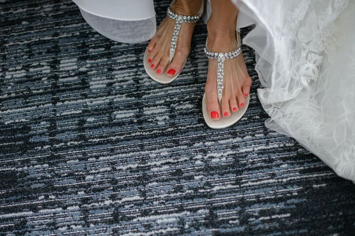 """To ensure maximum comfort on her wedding day, Alison wore a pair of gladiator sandals instead of traditional heels. The rhinestone-studded strap brought an element of flair to her elegant lace wedding gown. """"Since I hate heels, I was comfy as can be,"""" Alison says."""